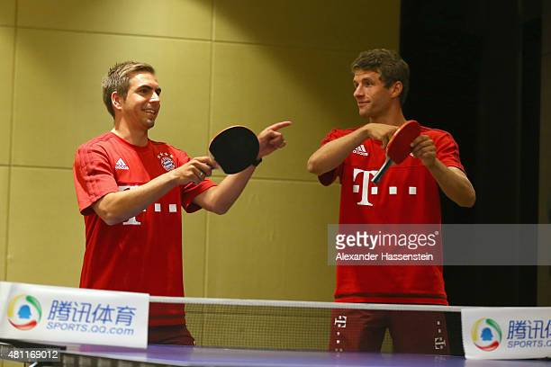 Philipp Lahm of FC Bayern Muenchen and his team mate Thomas Mueller plays a table tennis match broadcasted live on TV at Inter Continental Beijing...