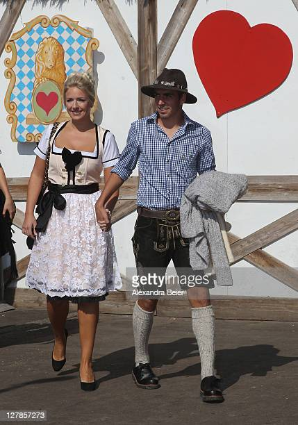 Philipp Lahm of FC Bayern Muenchen and his wife Claudia arrive for the Oktoberfest beer festival at the Kaefer Wiesnschaenke tent on October 2 2011...