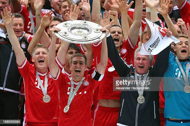 Philipp Lahm of FC Bayern Muenchen lifts the Bundesliga trophy with his team mates Bastian Schweinsteiger head coach Jupp Heynckes and Manuel Neuer...