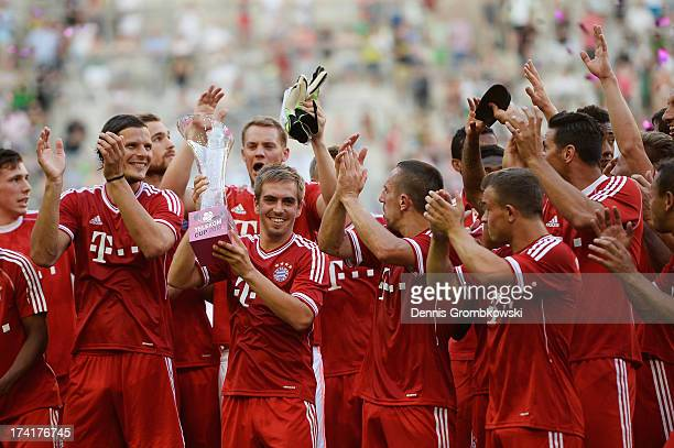 Philipp Lahm of FC Bayern Muenchen lifts the trophy after the Telekom 2013 Cup final between FC Bayern Muenchen and Borussia Moenchengladbach on July...