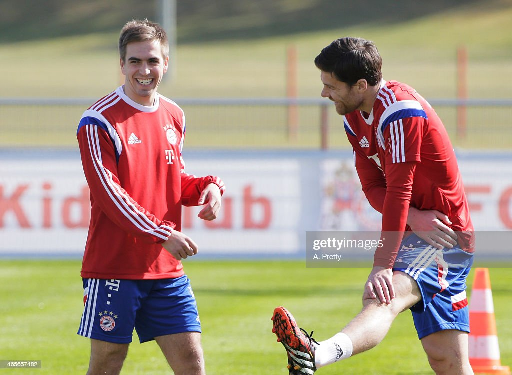 Philipp Lahm of FC Bayern Muenchen shares a laugh with Xabi Alonso during training on March 9, 2015 in Munich, Germany.