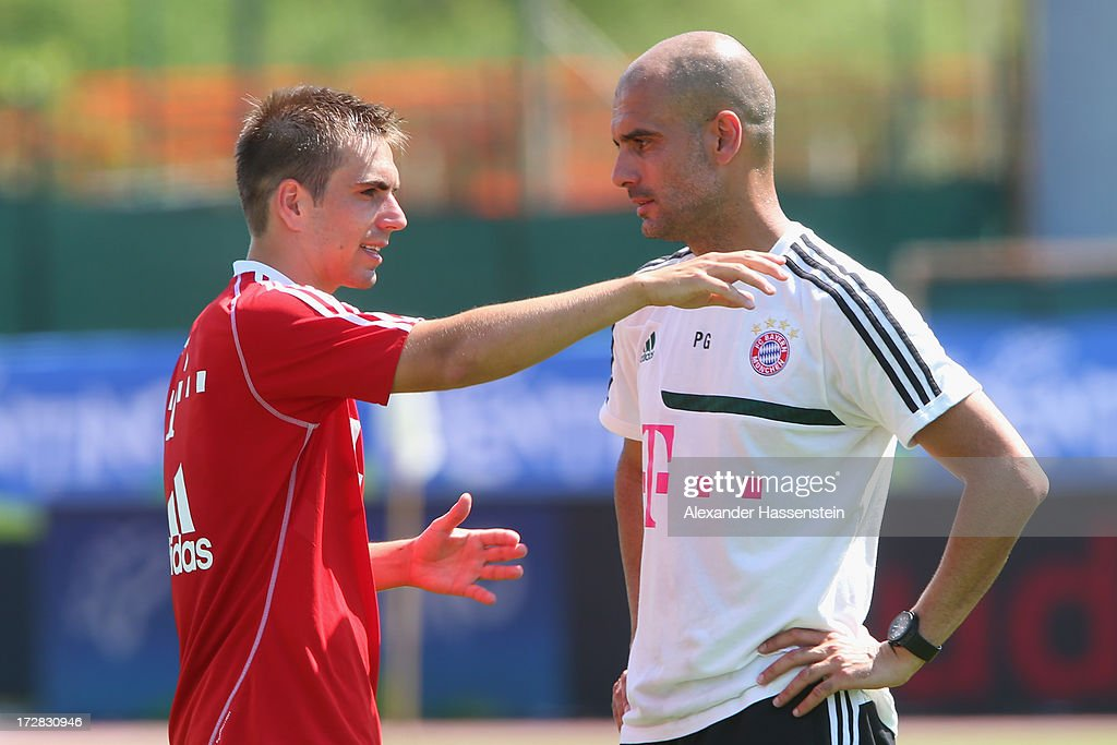 Philipp Lahm of FC Bayern Muenchen talks to his head coach Josep Guardiola during a training session at Campo Sportivo on July 5, 2013 in Arco, Italy.