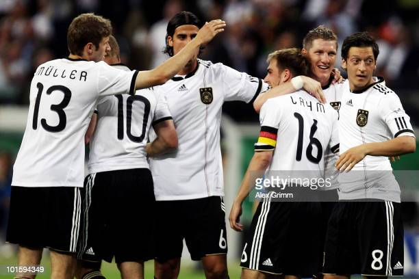 Philipp Lahm of Germany celebrates after scoring his team's first goal with team mates Thomas Mueller Lukas Podolski Sami Khedira Bastian...