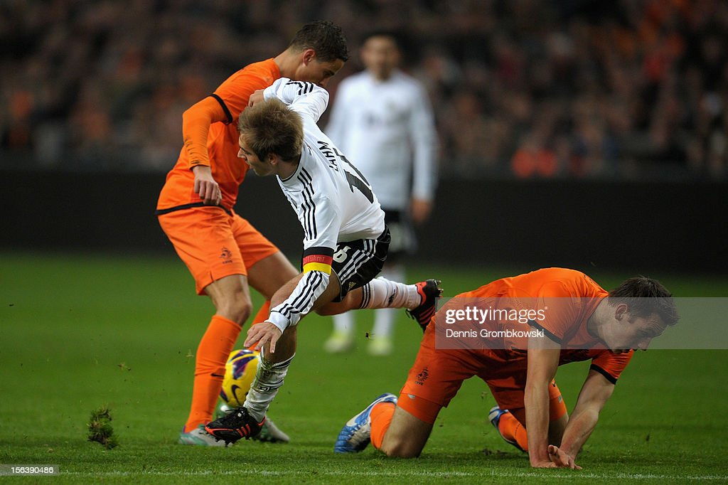 Philipp Lahm of Germany is challenged by Marco van Ginkel and Stefan de Vrij of Netherlands during the International Friendly match between Netherlands and Germany at Amsterdam Arena on November 14, 2012 in Amsterdam, Netherlands.