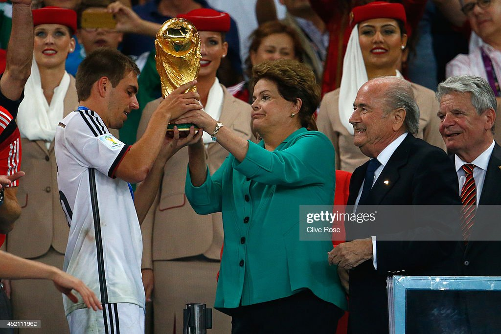 <a gi-track='captionPersonalityLinkClicked' href=/galleries/search?phrase=Philipp+Lahm&family=editorial&specificpeople=483746 ng-click='$event.stopPropagation()'>Philipp Lahm</a> of Germany is presented with the World Cup trophy by Brazilian President <a gi-track='captionPersonalityLinkClicked' href=/galleries/search?phrase=Dilma+Rousseff&family=editorial&specificpeople=1955968 ng-click='$event.stopPropagation()'>Dilma Rousseff</a> and FIFA President Joseph S. Blatter after defeating Argentina 1-0 in extra time during the 2014 FIFA World Cup Brazil Final match between Germany and Argentina at Maracana on July 13, 2014 in Rio de Janeiro, Brazil.