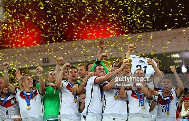 Philipp Lahm of Germany lifts the World Cup trophy to celebrate with his teammates during the award ceremony after the 2014 FIFA World Cup Brazil...