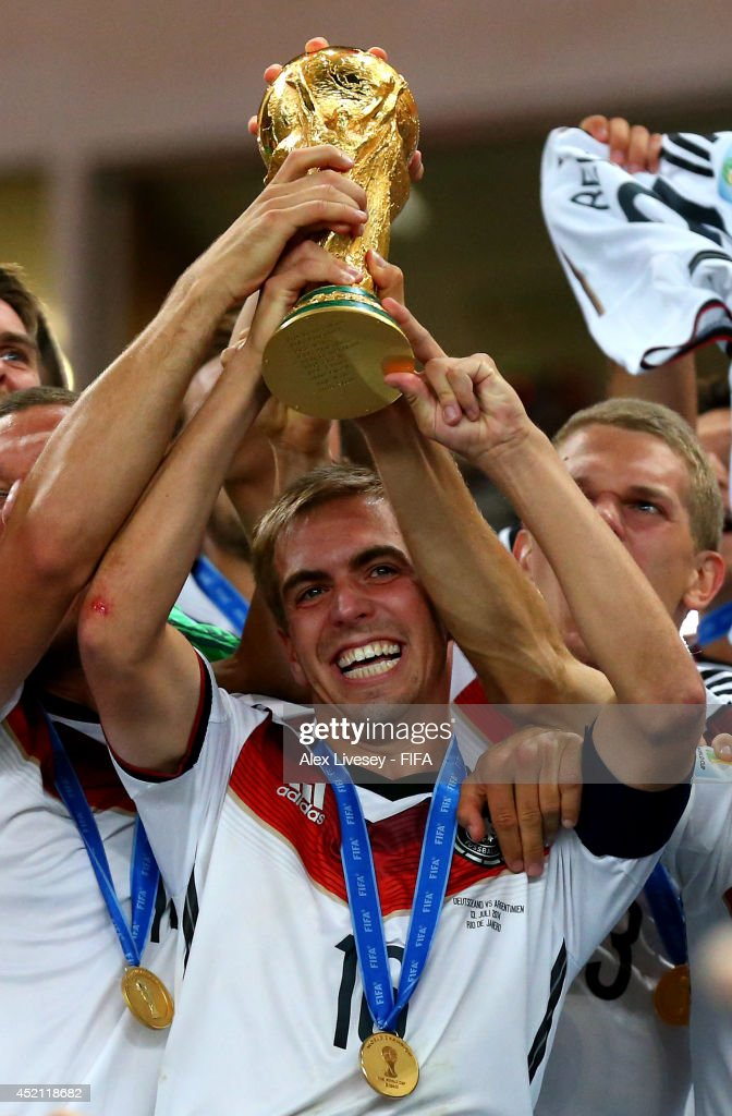 Philipp Lahm of Germany lifts the World Cup trophy to celebrate with his teammates during the award ceremony after the 2014 FIFA World Cup Brazil Final match between Germany and Argentina at Maracana on July 13, 2014 in Rio de Janeiro, Brazil.