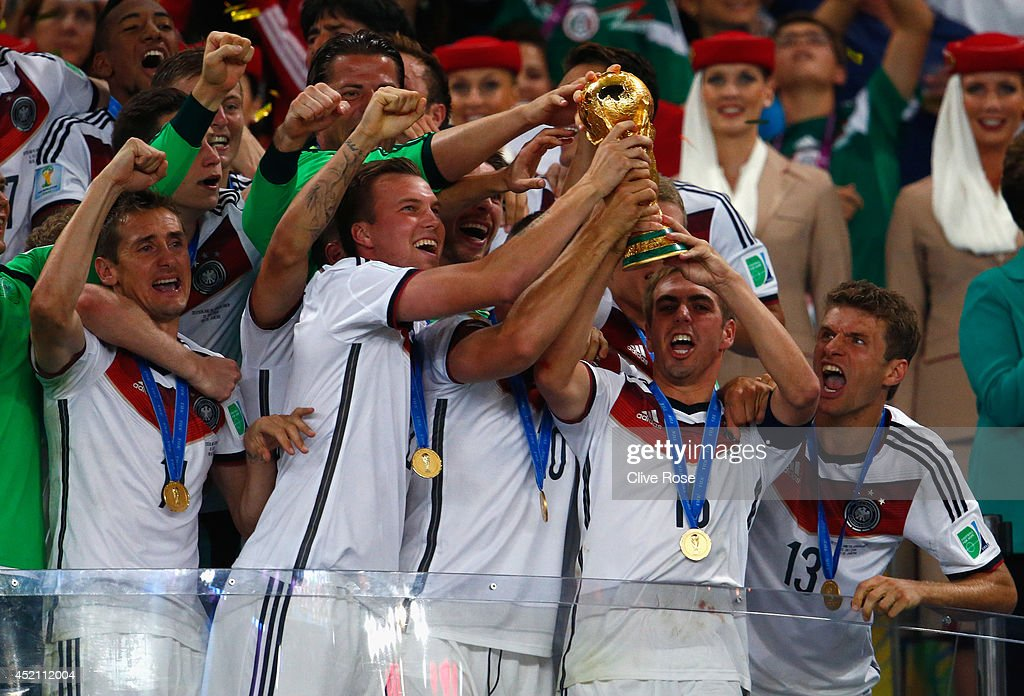 Philipp Lahm of Germany lifts the World Cup trophy with teammates after defeating Argentina 10 in extra time during the 2014 FIFA World Cup Brazil...