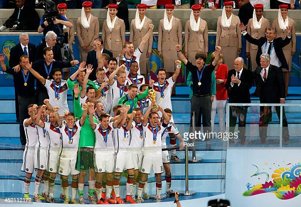 Philipp Lahm of Germany lifts the World Cup trophy with teammates after defeating Argentina 10 in extra time as FIFA President Joseph S Blatter...