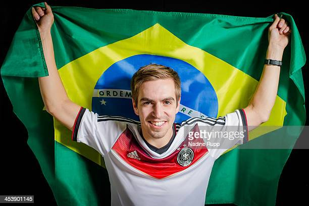 Philipp Lahm of Germany poses with the Brazilian flag ahead of the 2014 FIFA World Cup in Brazil on December 3 2013 in Munich Germany