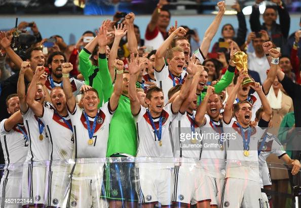Philipp Lahm of Germany raises the World Cup trophy with teammates after defeating Argentina 10 in the 2014 FIFA World Cup Brazil Final match between...