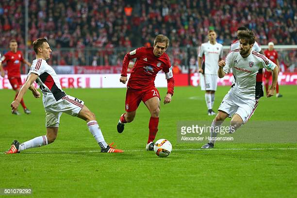 Philipp Lahm of Muenchen battles for the ball with Robert Bauer of Ingolstadt and his team mate Romain Bregerie during the Bundesliga match between...