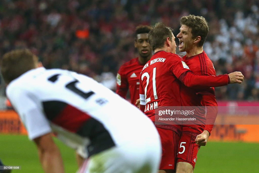 Philipp Lahm (L) of Muenchen celebrates scoring the 2nd team goal with his team mate Thomas Mueller during the Bundesliga match between FC Bayern Muenchen and FC Ingolstadt at Allianz Arena on December 12, 2015 in Munich, Germany.