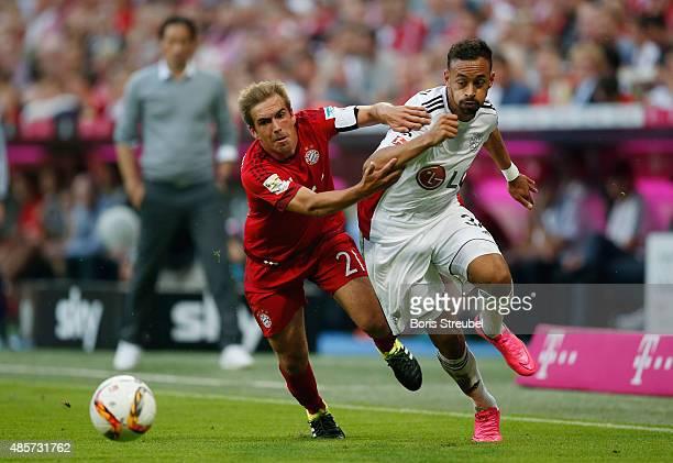 Philipp Lahm of Muenchen challenges Karim Bellarabi of Leverkusen during the Bundesliga match between FC Bayern Muenchen and Bayer 04 Leverkusen at...