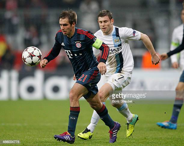 Philipp Lahm of Muenchen is challenged by James Milner of Manchester during the UEFA Champions League Group D match between FC Bayern Muenchen and...