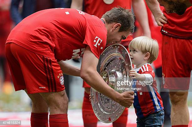 Philipp Lahm of Muenchen presents the Bundesliga trophy to his son Julian after winning the league during the Bundesliga match between FC Bayern...