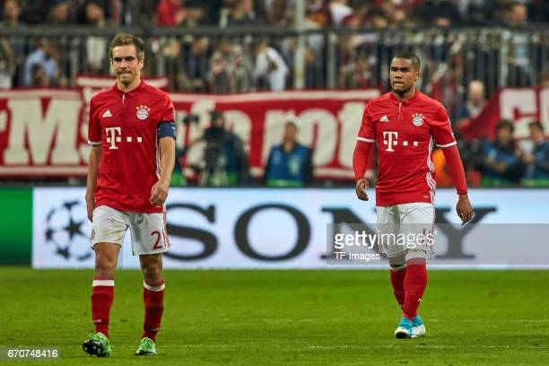 Philipp Lahm of Munich and Douglas Costa of Munich looks dejected during the UEFA Champions League Quarter Final first leg match between FC Bayern...