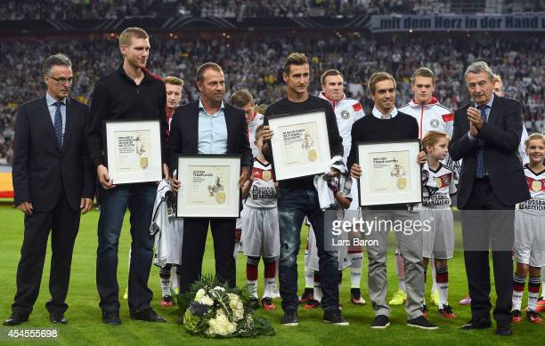 Philipp Lahm Per Mertesacker Miroslav Klose and assistant coach Hansi Flick of Germany are honored by DFB President Wolfgang Niersbach and Helmut...