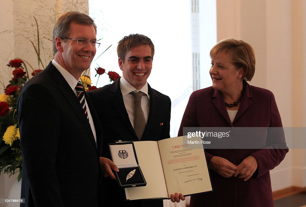 Philipp Lahm (C) smiles as he receives the Federal Cross of Merit from German Federal President Christian Wulff (R) and chancellor Angela Merkel (L) at Bellevue Castle on October 5, 2010 in Berlin, Germany.