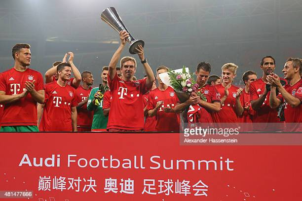 Philipp Lahm team captain of FC Bayern Muenchen lifts up the Audi Football Summit 2015 winners trophy after the international friendly match between...