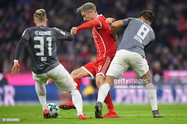 Philipp Max and Rani Khedira of Augsburg compete with Robert Lewandowski of FC Bayern Muenchen for the ball during the Bundesliga match between FC...