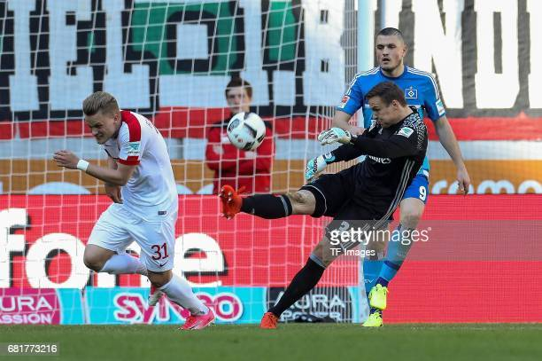 Philipp Max of Augsburg and Goalkeeper Tom Mickel of Hamburg battle for the ball during the Bundesliga match between FC Augsburg and Hamburger SV at...