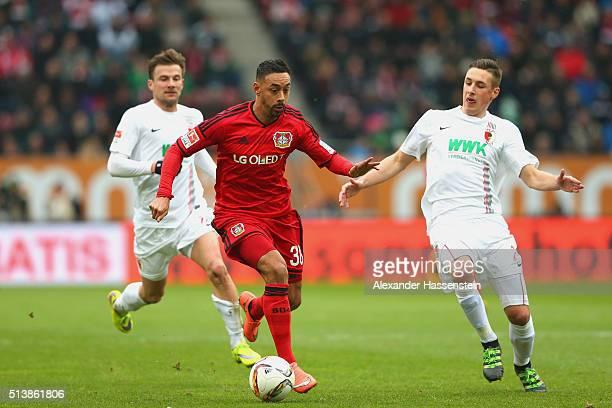 Philipp Max of Augsburg and his team mate Dominik Kohr battle for the ball with Karim Bellarabi of Leverkusen during the Bundesliga match between FC...