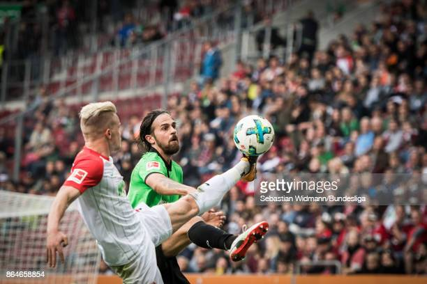 Philipp Max of Augsburg and Martin Harnik of Hannover 96 compete for the ball during the Bundesliga match between FC Augsburg and Hannover 96 at...