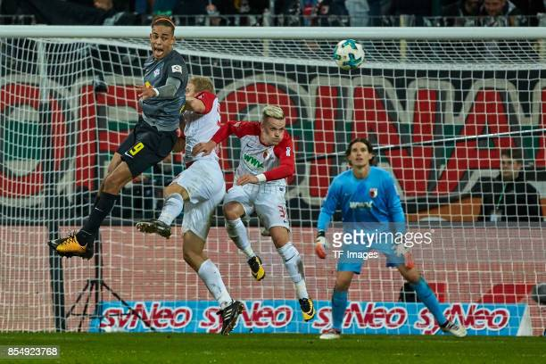 Philipp Max of Augsburg and Martin Hinteregger of Augsburg and Yussuf Poulsen of Leipzig battle for the ball during the Bundesliga match between FC...