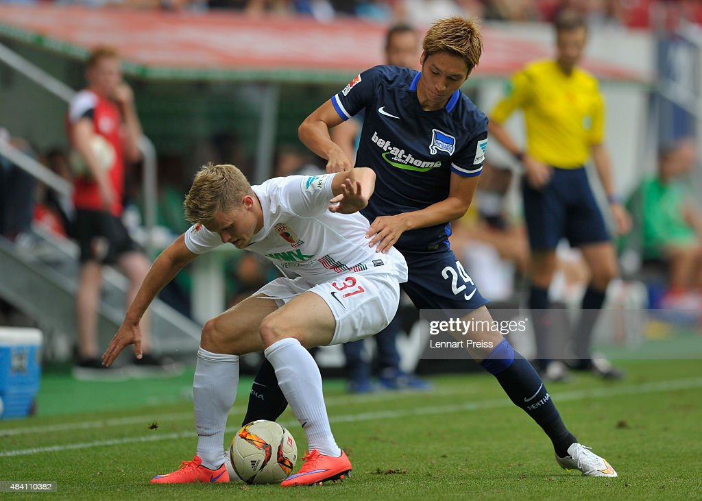 Philipp Max (L) of FC Augsburg challenges Genki Haraguchi of Hertha BSC during the Bundesliga match between FC Augsburg and Hertha BSC at WWK-Arena on August 15, 2015 in Augsburg, Germany.