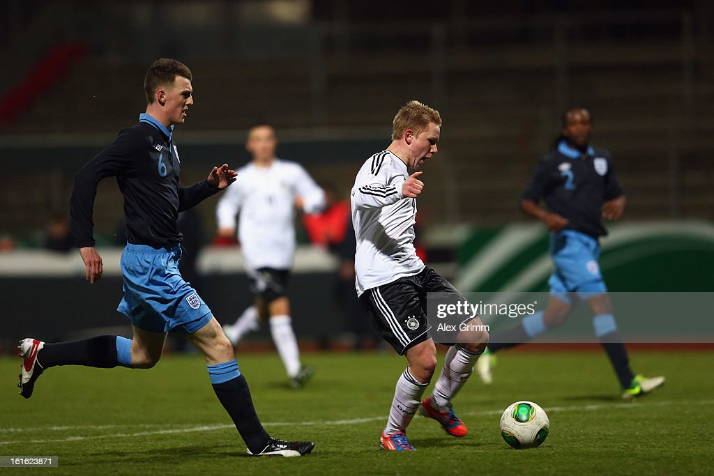 Philipp Ochs (R) of Germany scores his team's first goal against Kyle Cameron of England during the U16 international friendly match between Germany and England at Suedstadion on February 13, 2013 in Cologne, Germany.