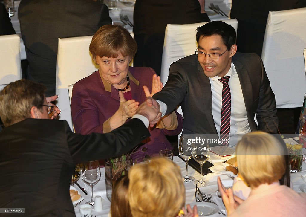 <a gi-track='captionPersonalityLinkClicked' href=/galleries/search?phrase=Philipp+Roesler&family=editorial&specificpeople=4838791 ng-click='$event.stopPropagation()'>Philipp Roesler</a> (R), Vice Chancellor and Chairman of the German Free Democrats (FDP), receives congratulations from Foreign Minister <a gi-track='captionPersonalityLinkClicked' href=/galleries/search?phrase=Guido+Westerwelle&family=editorial&specificpeople=208748 ng-click='$event.stopPropagation()'>Guido Westerwelle</a> as German Chancellor and Chairwoman of the German Christian Democrats (CDU) <a gi-track='captionPersonalityLinkClicked' href=/galleries/search?phrase=Angela+Merkel&family=editorial&specificpeople=202161 ng-click='$event.stopPropagation()'>Angela Merkel</a> looks on after Roesler spoke at his 40th birthday celebration on February 26, 2013 in Berlin, Germany. The FDP and CDU are the current German government coalition, though the FDP has faced a very challenging last 18 months that has brought the party to its lowest popularity ratings in decades. Germany faces federal elections in September.