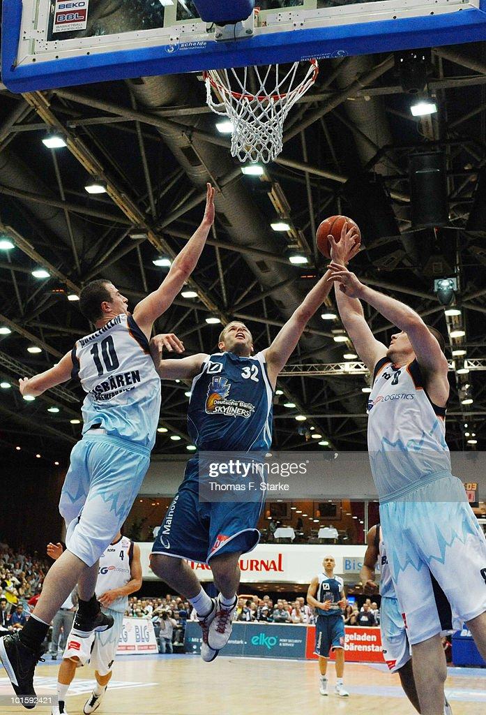Philipp Schwethelm and Andrew Drevo of Bremerhaven tackle Grayson Moyer of Frankfurt during the Beko Basketball Bundesliga playoff match between...