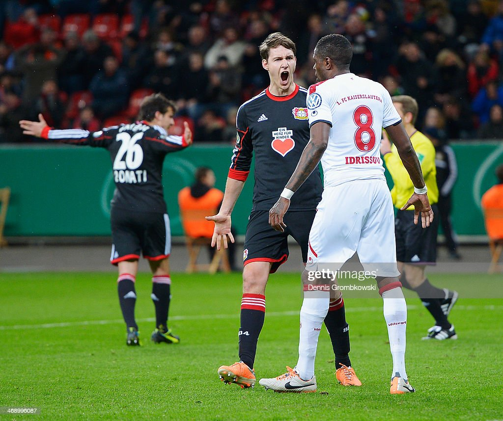 Philipp Wollscheid of Bayer Leverkusen reacts towards Mohamadou Idrissou of 1. FC Kaiserslautern who misses a chance at goal during the DFB Cup quarterfinal match between Bayer Leverkusen and 1. FC Kaiserslautern at BayArena on February 12, 2014 in Leverkusen, Germany.