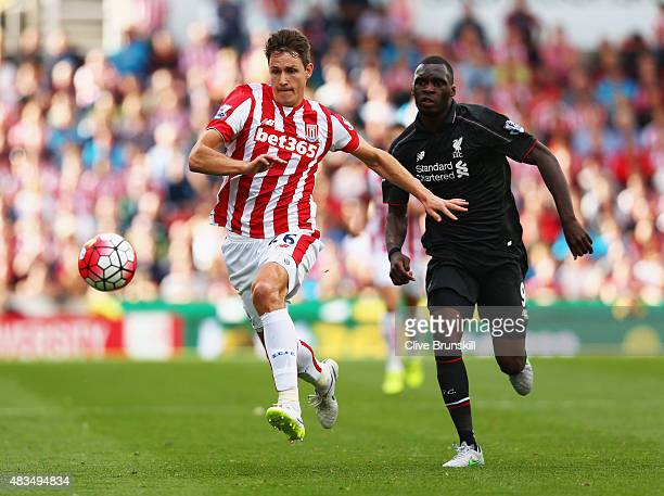 Philipp Wollscheid of Stoke City is chased by Christian Benteke of Liverpool during the Barclays Premier League match between Stoke City and...
