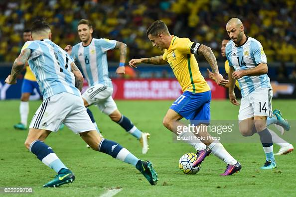 Philippe Coutinho of Brazil drives the ball as Javier Mascherano Nicolas Otamendi and Lucas Biglia of Argentina defend during a match between...