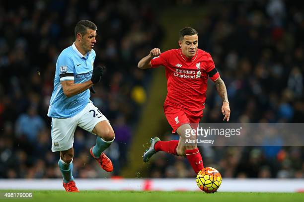Philippe Coutinho of Liverpool and Martin Demichelis of Manchester City compete for the ball during the Barclays Premier League match between...