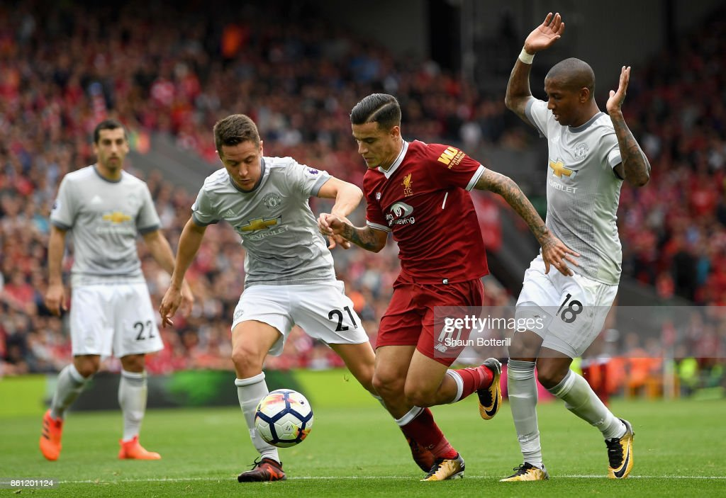 Philippe Coutinho of Liverpool battles for possession with Ander Herrera and Ashley Young of Manchester United during the Premier League match between Liverpool and Manchester United at Anfield on October 14, 2017 in Liverpool, England.