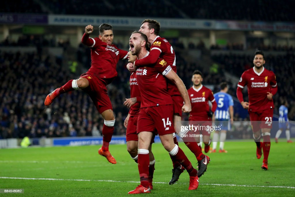 Philippe Coutinho of Liverpool celebrates with team-mates including Jordan Henderson after scoring his team's fourth goal during the Premier League match between Brighton and Hove Albion and Liverpool at Amex Stadium on December 2, 2017 in Brighton, England.