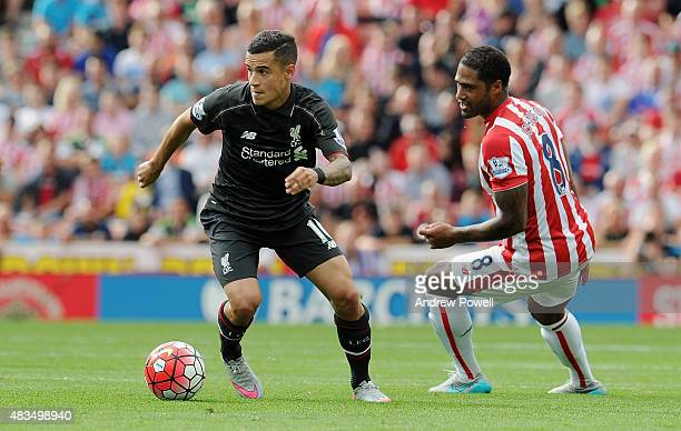 Philippe Coutinho of Liverpool competes with Glen Johnson of Stoke City during the Barclays Premier League match between Stoke City and Liverpool at...