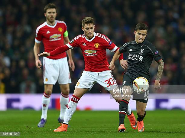 Philippe Coutinho of Liverpool evades Guillermo Varela of Manchester United during the UEFA Europa League round of 16 second leg match between...