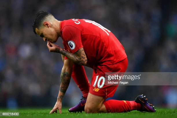 Philippe Coutinho of Liverpool goes down injured and holds his mouth during the Premier League match between Manchester City and Liverpool at Etihad...