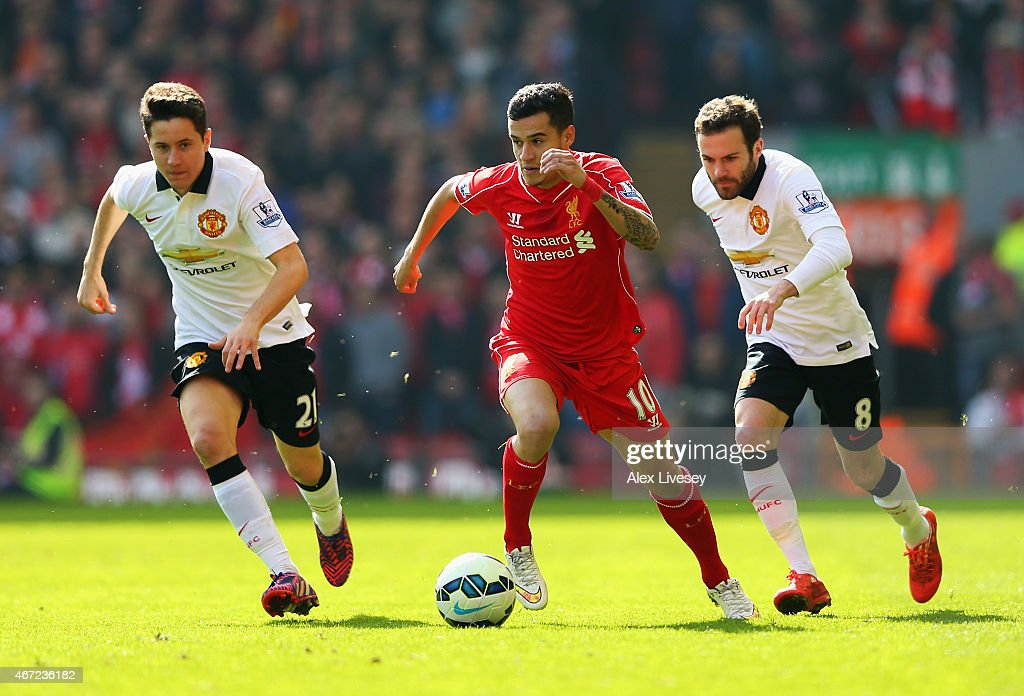 Philippe Coutinho of Liverpool goes past Ander Herrera (L) and Juan Mata of Manchester United during the Barclays Premier League match between Liverpool and Manchester United at Anfield on March 22, 2015 in Liverpool, England.