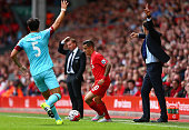 Philippe Coutinho of Liverpool in action as Brendan Rodgers of Liverpool looks on during the Barclays Premier League match between Liverpool and West...