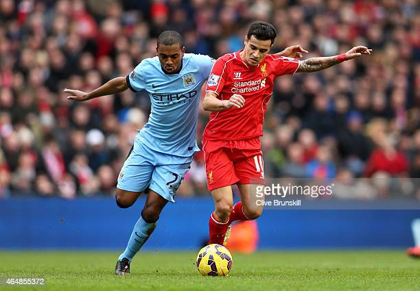 Philippe Coutinho of Liverpool is challenged by Fernandinho of Manchester City during the Barclays Premier League match between Liverpool and...