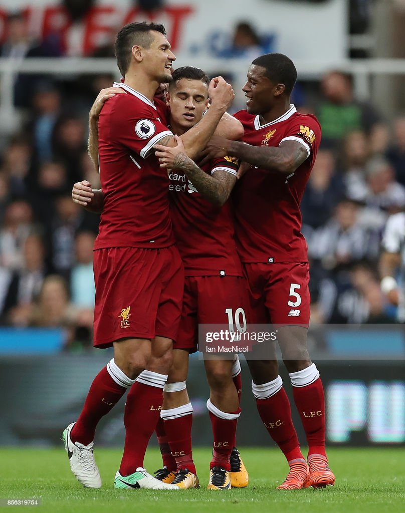 Philippe Coutinho of Liverpool is congratulated by team mates after he scores the opening goal during the Premier League match between Newcastle United and Liverpool at St. James Park on October 1, 2017 in Newcastle upon Tyne, England.