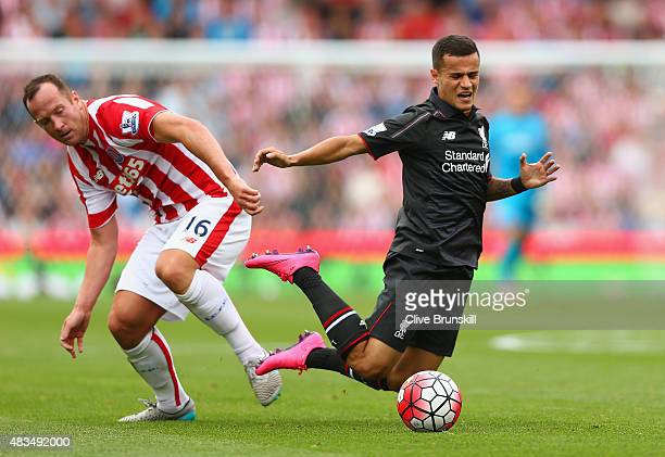 Philippe Coutinho of Liverpool is tackled by Charlie Adam of Stoke City during the Barclays Premier League match between Stoke City and Liverpool at...