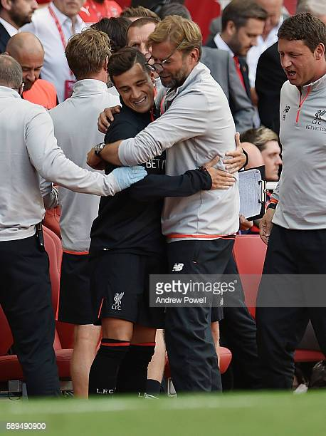 Philippe Coutinho of Liverpool knocks the glasses of his manager Jurgen Klopp during the Premier League match between Arsenal and Liverpool at...