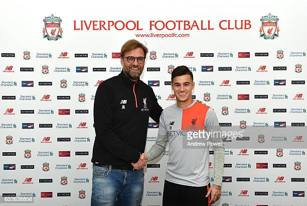 Philippe Coutinho of Liverpool poses after signing a new contract with Jurgen Klopp manager of Liverpool at Melwood Training Ground on January 24...