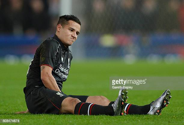Philippe Coutinho of Liverpool reacts after going down with an injury during the Capital One Cup semi final first leg match between Stoke City and...
